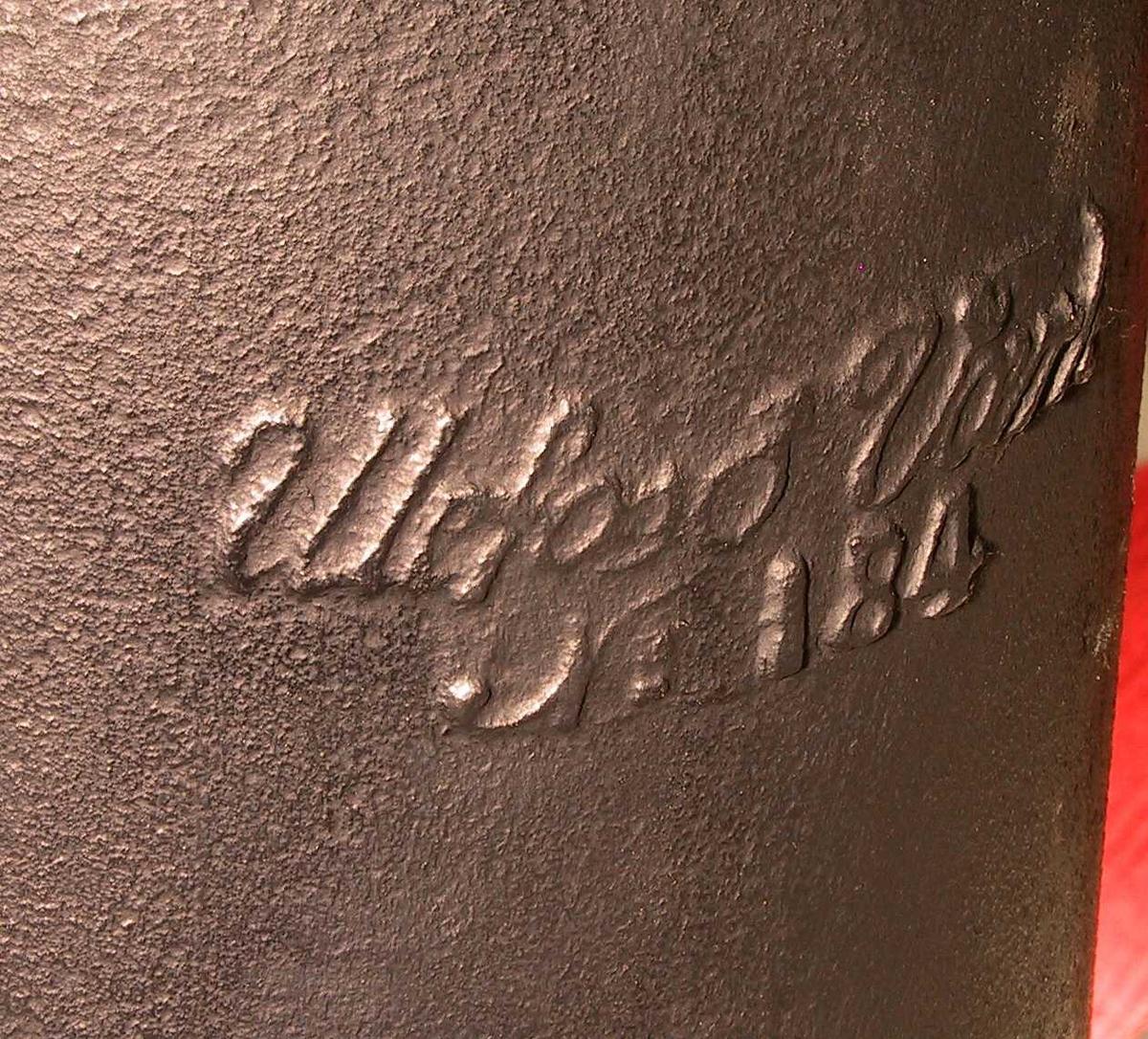 Liten sylinderovn. Støpejern,  på baksiden produsentnavn.  Lavt, kvadratisk postament  m/ avskrådde hjørner, på fronten stor askeskuff m. ventilhull og bøylehank.  På hjørnene festet korte ben i palmett  og C form. Over postamentet sylindrisk fyrkasse, glatt, m.  profilert base og gesims, i fronten  hengslet dør prydet m. lavt relieff  i nyrokokko, svungen kant oppe og nede,  og svunget håndtak m. knott.  Øvre sylinder med mindre diameter, kannelert, på midten tverrbånd m.  relieffornamenter. Øverst gesims  og tunget kant, herover gjennombrutt hvelvet lokk m. stor knapp.  Tilstand 1988 god.