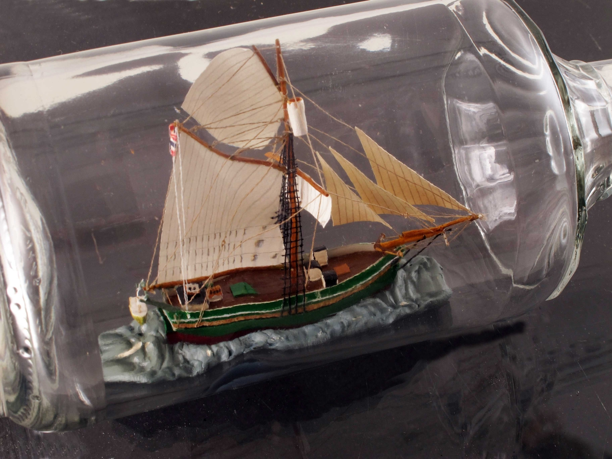 """Jakten """"Gjøa"""", Roald Amundsens skip gjennom Nordvestpassasjen 1903-1906. Grønnmalt skrog med sort og hvit stripe. Norsk flagg i riggen."""