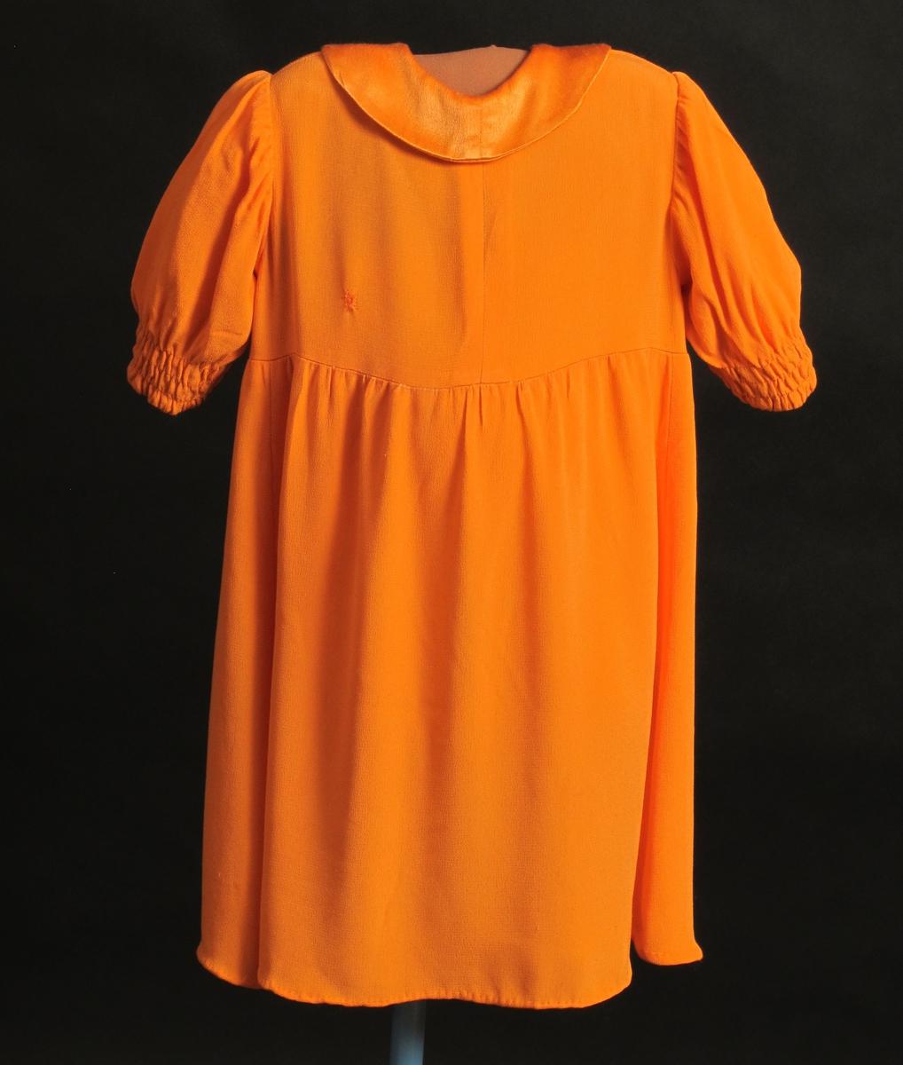Barnekjole av silke, chepe de chine. Orange.  Maskinsøm. Sydd med hvit tråd - det var vanskelig å skaffe sytråd i 1945. Lukkes med trykknapper.