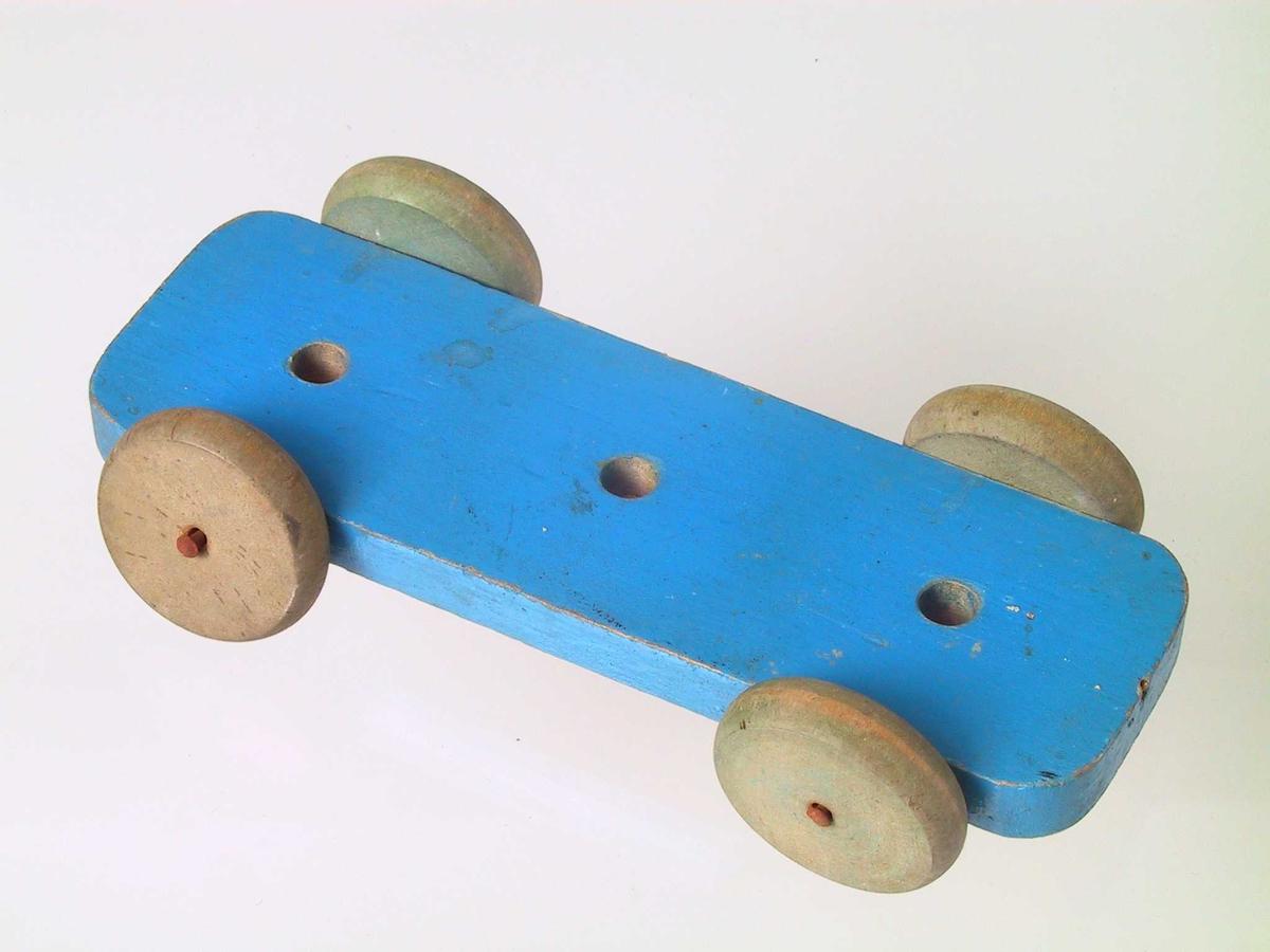 Form: Treplate med fire hjul, tre hull på oversiden, disse har trolig blitt brukt til å feste en del av bilen som nå mangler.