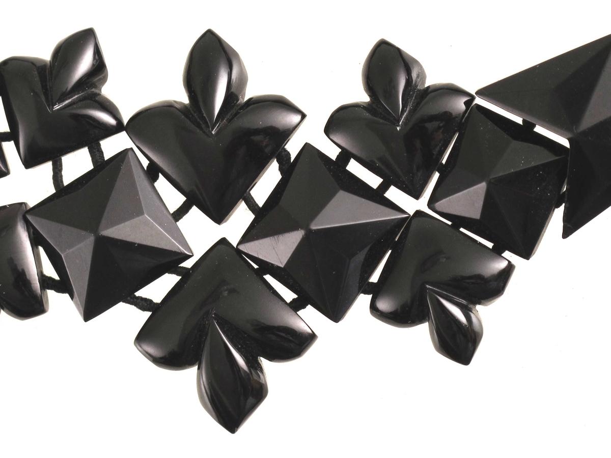"""Firkanter og """"liljer"""", flate på baksida. 2 gjennomgående hull. Tredd på 2 tråder, knyttet sammen til smykke. For stort til å være armbånd, har det opprinnelig vært et halssmykke som har mistet noen ledd?"""