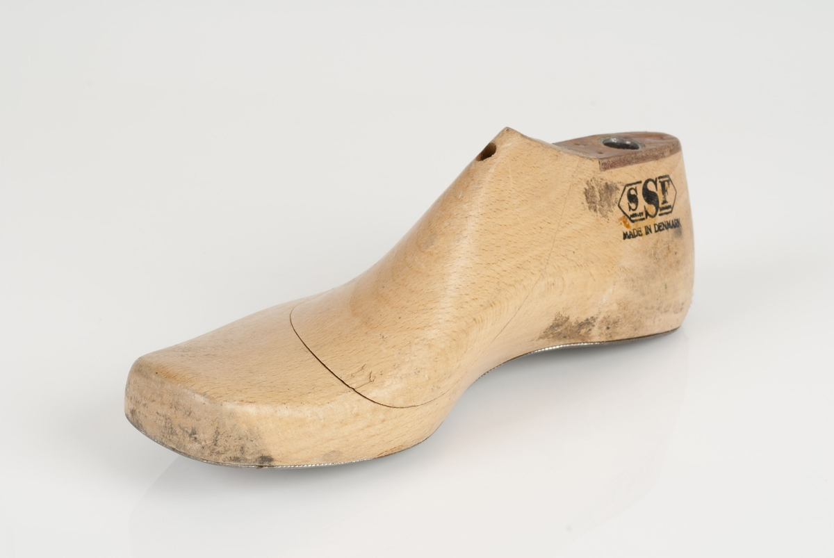 En tremodell i to deler; lest og opplest/overlest (kile). Høyrefot i skostørrelse 34, og 8 cm i vidde. Lestekam i skinn. Såle i metall.