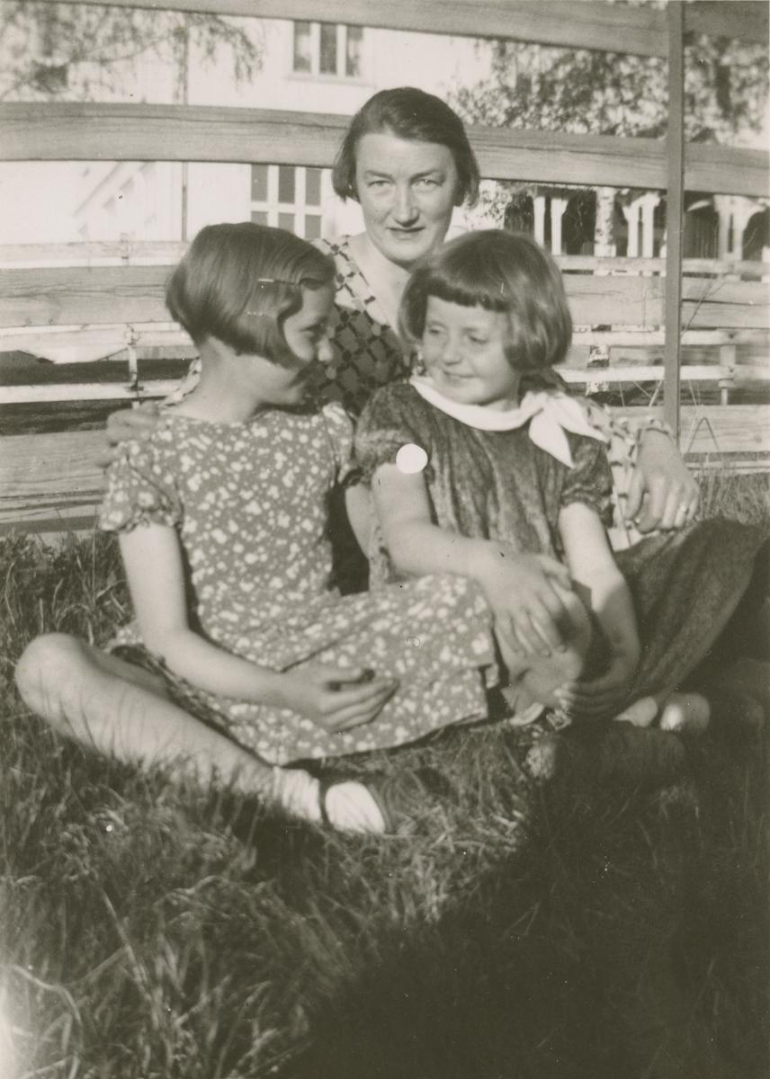 Fru Moe sitter i gresset med de to små jentene Åse Moe og Liv Frogner.