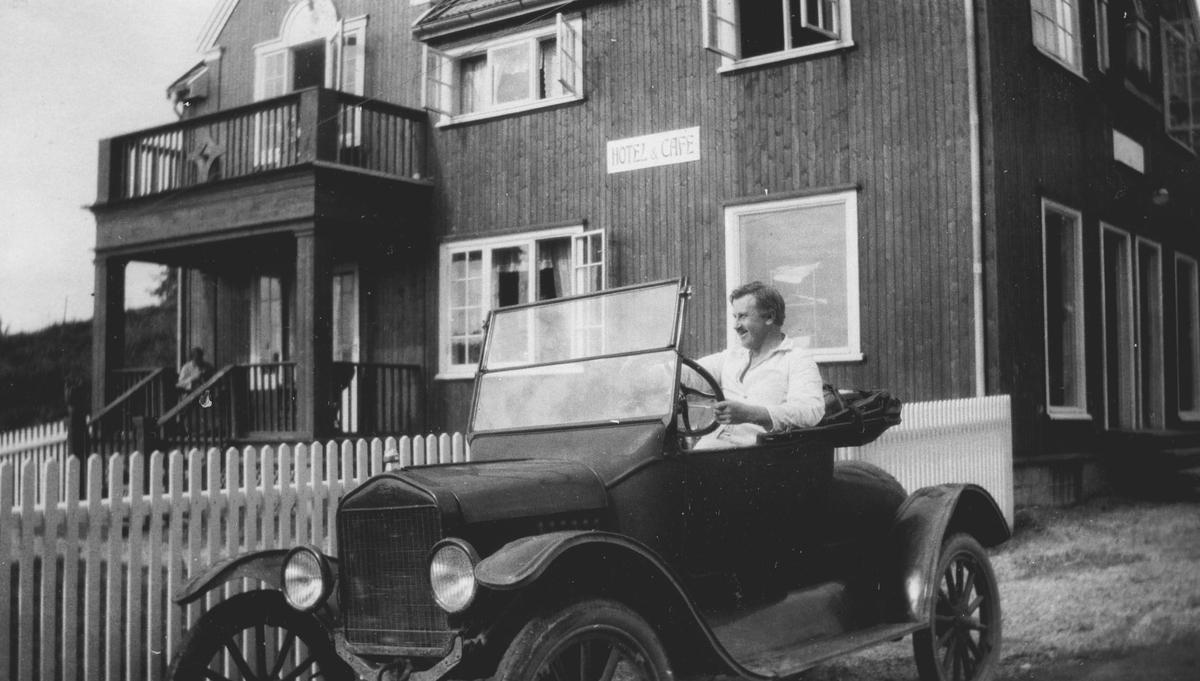 Ivar M. Mørkved i bil utenfor butikken (hotell og café)