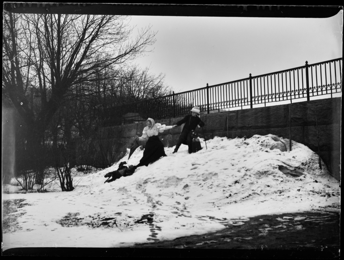 To barn og en dame i snøen.
