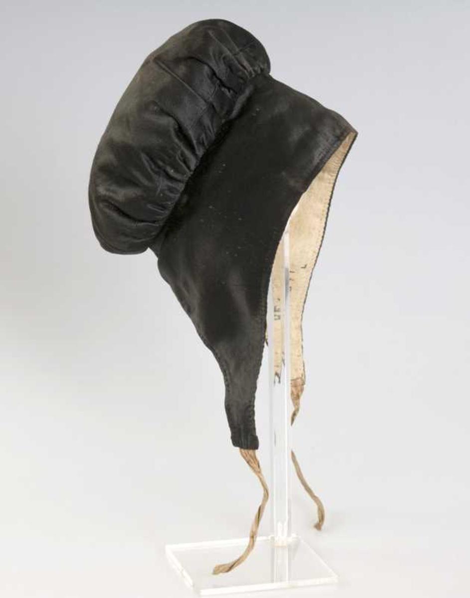 Høglue i svart silkesateng med stripete knytteband. Fôr av hvitt lin.