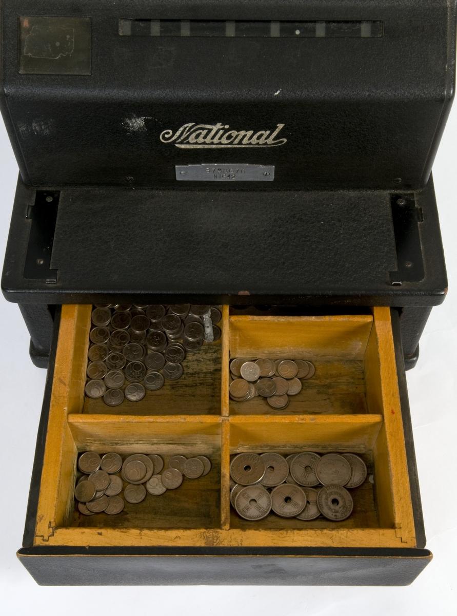 Sort kassaapparat med pengeskuff og sveiv. Maks innslag 99 kroner og 99 øre.